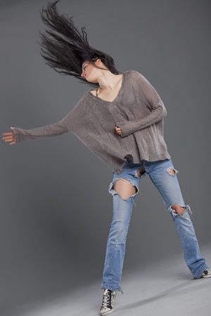 ripped jeans: hip hop woman dancing in studio over grey background