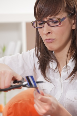 frustrated woman cuts credit card with scissors at home photo