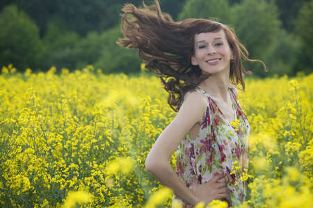 woman in summer dress running through yellow field photo