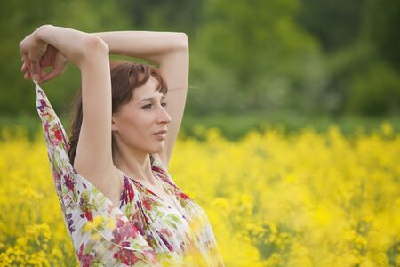 happy woman in yellow spring field  photo