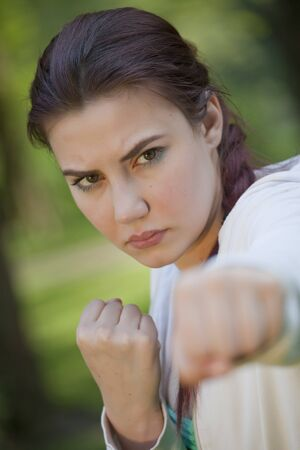 young woman in fighting stance and punching exercises Stock Photo - 9575260