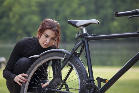 fitness woman has a trouble with mountain bike outdoors photo