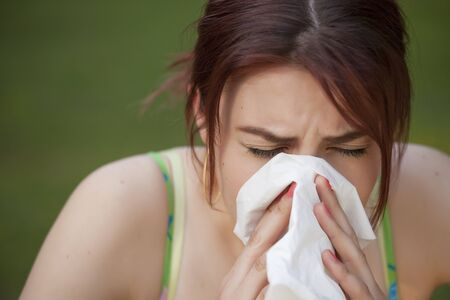 young woman with a an allergy sneezing into her handkerchief Stock Photo