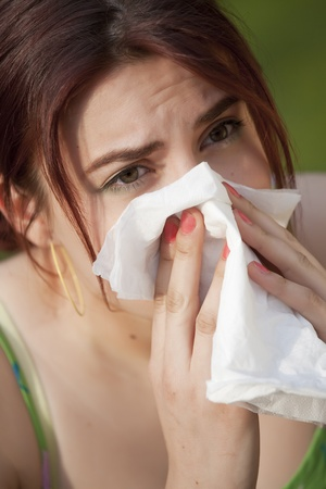 young woman with pollen allergy sneezing in handkerchief Stock Photo