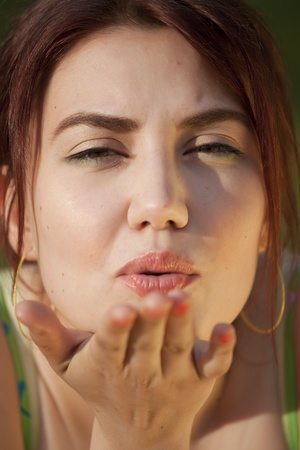 young woman sending air kiss in camera photo