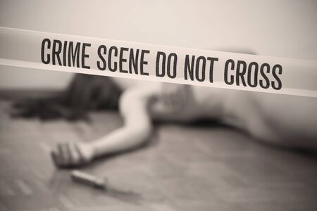 gruesome: crime scene - nude woman lying dead on the ground, focus on boundary tape Stock Photo