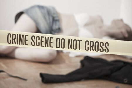 crime sceme - abused and dead woman lying on the ground