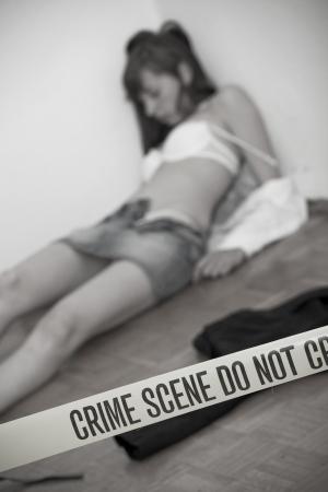hostage: crime scene - dead woman, focus on boundary tape Stock Photo