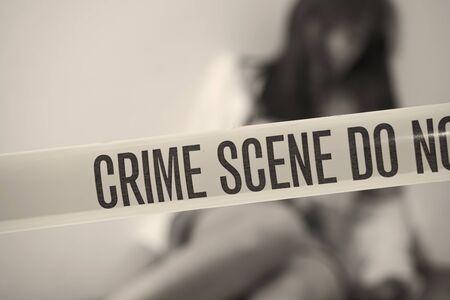 violencia sexual: escena del crimen - mujer jugando con cinta de l�mite en primer plano