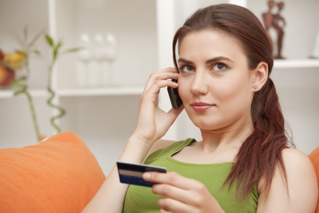 young woman holding credit card and making purchase on cell phone photo