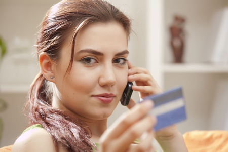 young woman with credit card and mobile phone photo