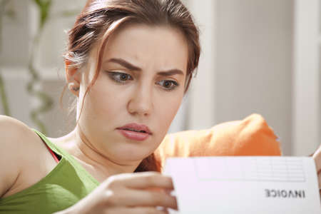 shocked young woman holding bill at home photo