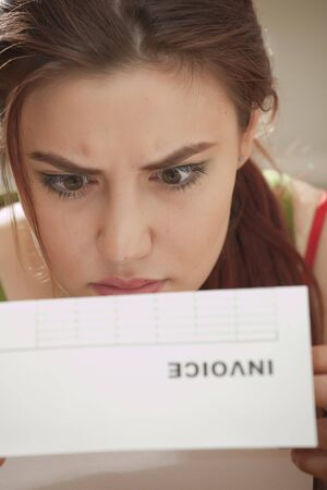 shocked face: shocked woman looking at bill amount letter