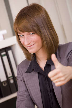 woman in business suit with thumb up by office work photo