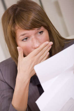 shocked woman reading a letter - bad news or fired photo
