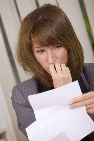 envelope with letter: donna d'affari scioccato leggendo una lettera con una cattiva notizia