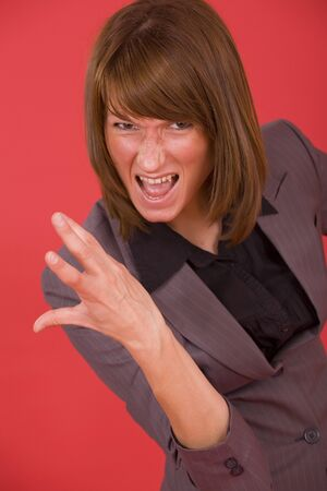 frustrated and screaming business woman over red background photo