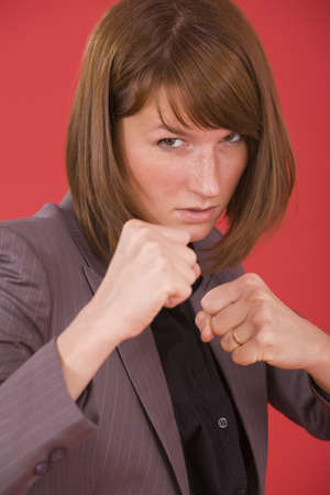business woman in fighting stance on red background photo