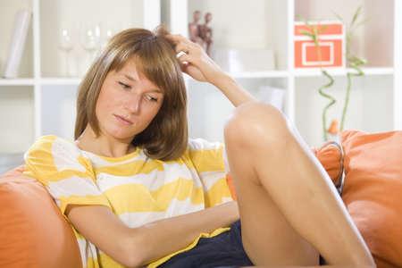 sad woman sitting on sofa in living room Stock Photo - 9967377