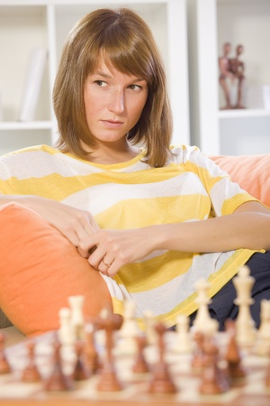 thinking woman sitting on sofa in front of chess game photo