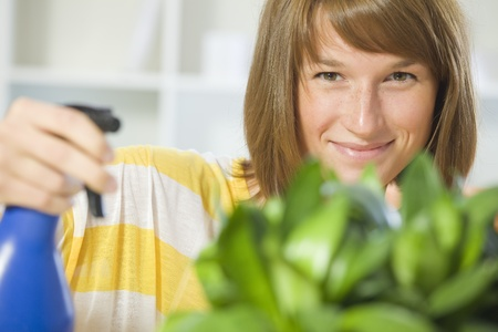 young woman watering potted plants at home photo