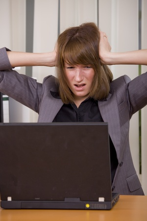 stressed businesswoman holding her head with both hands looking at laptop photo