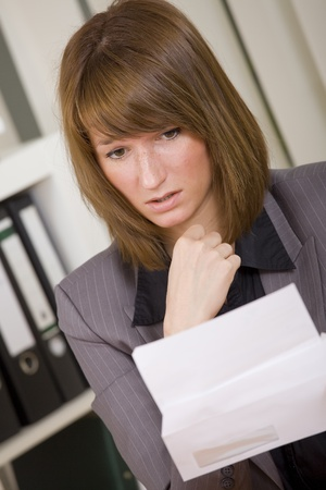 news letter: woman reading a letter with bad news Stock Photo