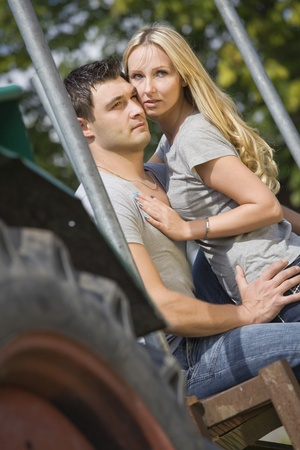 young couple sitting on tractor in countryside photo