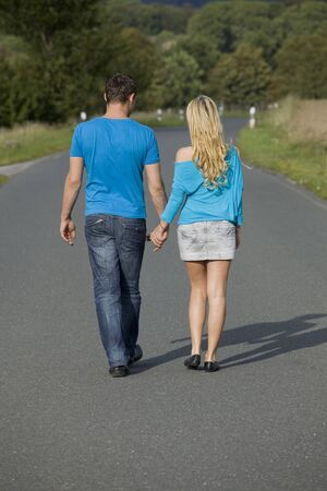 countryside loving: happy couple walking on the road holding hands
