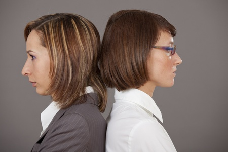 concurrent: two sad business women standing back on back over grey background Stock Photo