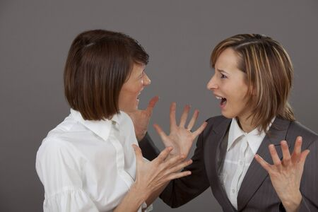 concurrent: two business women in dispute over grey background