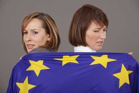 two business women pulling on european flag to each side photo