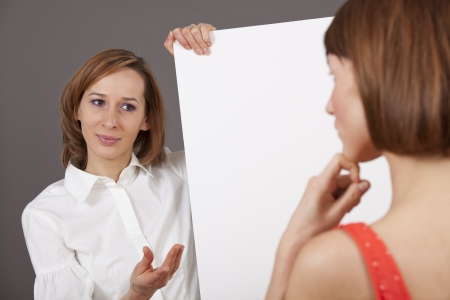 coaching talk - woman holding a blank board talking to a customer Stock Photo