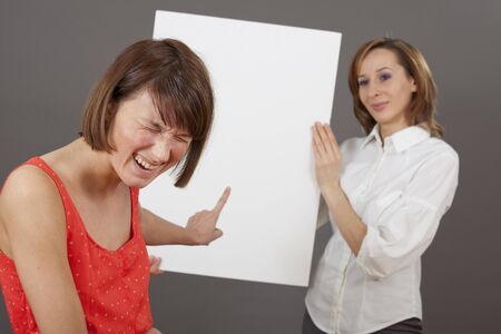 woman laughing about a businesswoman which holding a blank white board - for personal message or sales offer  photo