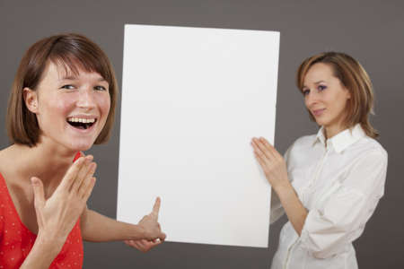 special offer or great deal - happy woman pointing with a finger on blank board photo