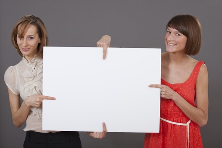 two women holding a white banner and pointing with fingers at the middle photo
