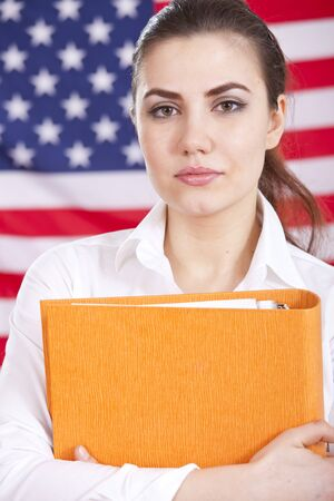 portrait of female student holding a folder over american flag photo