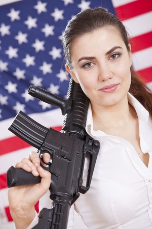 portrait of patriotic woman with machine gun over american flag photo