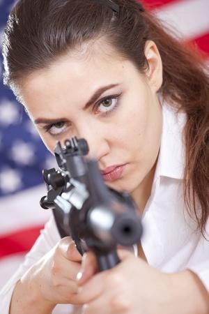 gun control: young woman over american flag aiming with machine gun