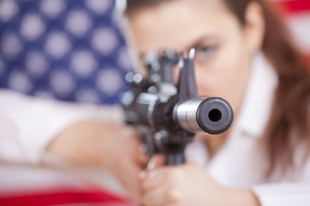 woman aiming with machine gun over american flag - focus on gun barrel photo