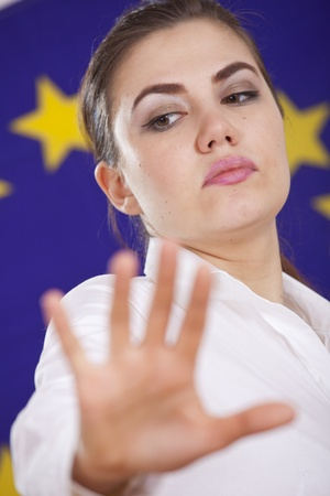 stop hand sign from a woman standing over european flag photo