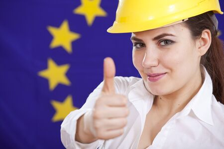 thumb up for european economy - happy woman in safety helmet over european flag photo