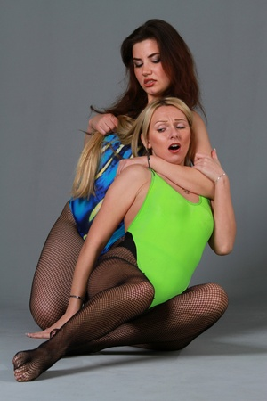 female wrestling: two women in aerobic leotards fighting over grey background Stock Photo