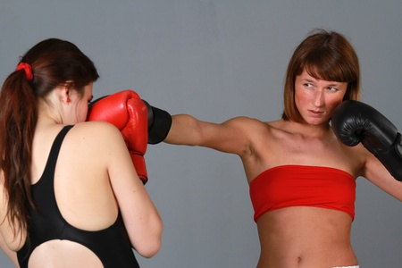 struggles: two women boxing over grey background Stock Photo