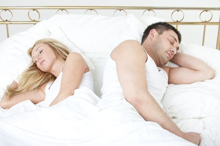 Couple sleeping back on back in bed photo