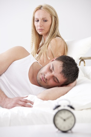 Frustrated woman in bed looking at sleeping man - alarm clock in foreground photo