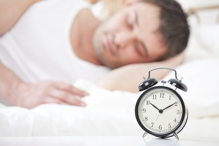 Man sleeping with alarm clock in foreground Stock Photo - 13135861