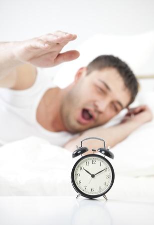 obudził: Człowiek śpi jest obudzony przez budzik Zdjęcie Seryjne