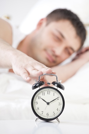 Sleeping man reaching for ringing alarm clock photo
