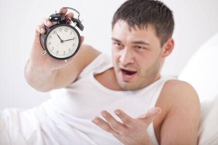 angry man in bed holding alarm clock in his hand photo